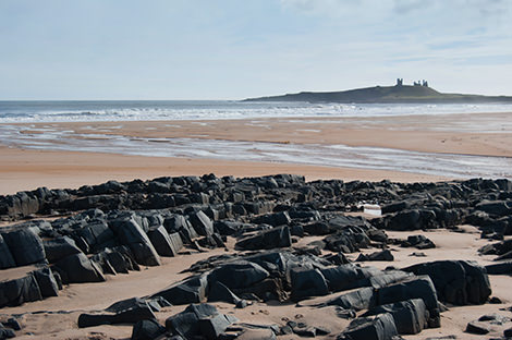 The ruins of Dunstanburgh Castle seen from Embleton Bay